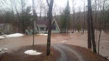 A cottage in Waterford, N.B., is surrounded by flood waters on April 16, 2014. (GILLES DAIGLE/THE CANADIAN PRESS)