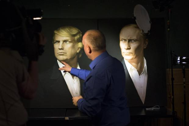 A journalist points at a portrait of Donald Trump and Russian President Vladimir Putin during a live telecast of the U.S. presidential election in the Union Jack pub in Moscow on Nov. 9, 2016.