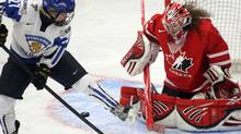 Team Canada's goaltender Shannon Szabados stops Team Finland's Anne Helin during first period action at the World Women's Ice Hockey Championships Sunday. Canada won 3-2. (Ryan Remiorz/Ryan Remiorz/THE CANADIAN PRESS)