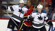 San Jose Sharks' Colin White, left, and Jamie McGinn sandwich Calgary Flames' Tom Kostopoulos. (Jeff McIntosh/The Canadian Press/Jeff McIntosh/The Canadian Press)