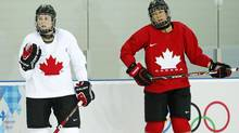 Canada's former team captain and flag bearer Hayley Wickenheiser, left, stands with new team captain Caroline Ouellette during their women's ice hockey team practice ahead of the 2014 Sochi Winter Olympics February 4, 2014. (MARK BLINCH/REUTERS)