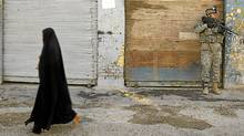 An Iraqi woman walks past a U.S. soldier on patrol in the Sheikh Ali Muslim Sunni neighbourhood in Baghdad in March, 2007. (PATRICK BAZ/Patrick Baz/AFP/Getty Images)