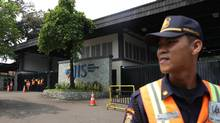 A security guard stands at the entrance of Jakarta International School in this photo taken in May. (Achmad Ibrahim/The Associated Press)