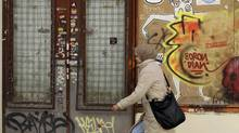 In this photo taken Saturday, April 14, a woman walks past a closed store in Madrid. Spain is the latest country in the hot seat of the euro zone debt crisis. (Alberto Di Lolli/Alberto Di Lolli/Associated Press)