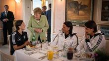 In this picture taken Wednesday June 6, 2012 and publicly provided by the German Governments press office, German chancellor Angela Merkel, foreground second left, talks to German national soccer player Mesut Oezil, left, while other members of the German squad, Tim Wiese, second right and Sami Khedira listen, at a meeting for dinner in Gdansk Poland. (Guido Bergmann/AP)