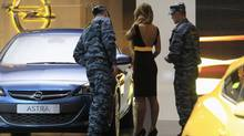 Russian policemen and an assistant look at an Opel Astra during preparations for the Moscow International Automobile Salon on Thursday, Aug. 29, 2012. One million people are expected to visit the show, which opens to the public Friday. (SERGEI KARPUKHIN/REUTERS)