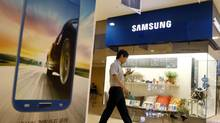 A man using his mobile phone walks past a Samsung Electronics shop in the company's main office building in central Seoul July 23, 2013. (LEE JAE-WON/REUTERS)