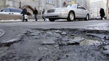 Motorists steer past a pothole on a Montreal street. (Paul Chiasson/CP)