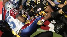 Montreal Alouettes wide receiver Tyron Carrier (L) is tackled during the first half of the 2013 CFL Touchdown Atlantic game against the Hamilton Tiger-Cats in Moncton, New Brunchwick, September 21, 2013. (DEVAAN INGRAHAM/REUTERS)