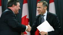 Canadian Finance Minister Jim Flaherty, left, shakes hands with Bank of Canada Governor Mark Carney after it was announced in Ottawa, Monday Nov. 26, 2012 that Carney will be the new head of bank of England. (FRED CHARTRAND/THE CANADIAN PRESS)