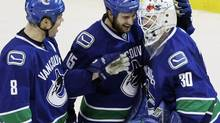 Vancouver Canucks Andrew Raycroft (R) celebrates his shutout win over the Colorado Avalanche with teammates Willie Mitchell (L) and Tanner Glass at the conclusion of NHL hockey action in Vancouver, British Columbia, November 1, 2009. REUTERS/Lyle Stafford (LYLE STAFFORD)