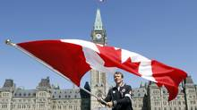 Triathlete Simon Whitfield of British Columbia waves the Canadian flag after it was announced Thursday July 12, 2012 in Ottawa that he would be the official flag bearer at the upcoming London Olympics. (Fred Chartrand/THE CANADIAN PRESS)