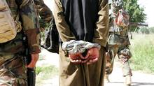 A man Afghan authorities suspect of insurgency-related activities is interrogated during a joint Canadian-Afghan army patrol in the Panjwaii District of Kandahar province on July 2, 2009. (COLIN PERKEL)