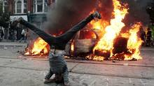 A man does a handstand in front of a burning police car during a G20 protest in downtown Toronto on June 26, 2010. (Mark Blinch/Reuters)