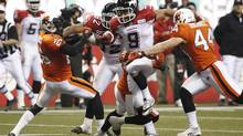 Calgary Stampeders Jon Cornish (C) runs against the BC Lions Anthony Reddick (L) and Adam Bighill (R) during the second half of the CFL's Western Conference Final game in Vancouver, British Columbia, November 18, 2012. (ANDY CLARK/REUTERS)