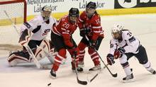 Canadian forwards Jennifer Wakefield (#20) and Jayna Hefford (#16) battle for the puck with USA Josephine Pucci (#24) in front of the USA goaltender Molly Schaus (#1) and Defense Josephine Pucci (#24) during the first period of the gold medal game at the Four Nations women's hockey action in St. John's on Saturday Nov. 13, 2010. THE CANADIAN PRESS/Paul Daly (Paul Daly)