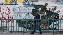 A Hamas policeman walks past a mural depicting an exploded Israeli tank, in Gaza City Nov. 22, 2012. (MOHAMMED SALEM/REUTERS)