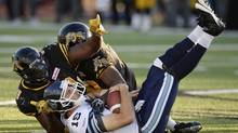 Toronto Argonauts quarterback Ricky Ray is sacked by Hamilton Tiger-Cats' Torrey Davis during first half CFL action in Guelph, Ont., Monday, Oct.14, 2013. (FRANK GUNN/THE CANADIAN PRESS)
