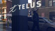 A pedestrian is reflected in the window of a Telus store while using a mobile phone in Ottawa February 11, 2011. The Vancouver-based telecom giant will hire 900 people across Ontario in 2012 as it rolls out its next-generation wireless network, noting those new positions as part of the company's broader plan to hire more than 3,000 people across the country this year. Chris Wattie (CANADA - Tags: BUSINESS) (© Chris Wattie / Reuters/Chris Wattie / Reuters)