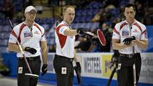 Canada skip Brad Jacobs, centre, and teammates Ryan Harnden, left, and E.J. Harnden discuss their next move during their game against the Czech Republic at the World Men's Curling Championships in Victoria, British Columbia April 2, 2013. (ANDY CLARK/REUTERS)