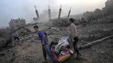 Palestinians try to salvage what they can of their belongings from the rubble of a house destroyed by an overnight Israeli air strike in Gaza City on Tuesday. By Tuesday afternoon, as many as 15 Palestinians were killed in the Israeli operation, dubbed Operation Protective Edge. (KHALIL HAMRA/ASSOCIATED PRESS)