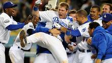 Los Angeles Dodgers' A.J. Ellis is mobbed at home plate by teammates after hitting a three run home run to beat the Houston Astros 6-3 in the ninth inning of a baseball game in Los Angeles on Saturday, May 26, 2012. (AP Photo/Keith Birmingham, Pasadena Star-News) (Keith Birmingham/AP)