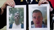 RCMP Insp. Tim Shields holds up photos of Angus David Mitchell during a news conference in Burnaby, B.C., on May 30, 2012. (Jonathan Hayward/The Canadian Press)