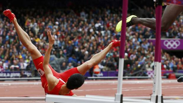 China's Liu Xiang falls onto the track during his men's 110m hurdles round 1 heat at the London 2012 Olympic Games at the Olympic Stadium August 7, 2012.