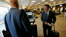 Robert Deluce, president of Porter Airlines, right, checks in with gate staff while boarding a flight in Toronto (J.P. MOCZULSKI/J.P. MOCZULSKI/THE GLOBE AND MAI)