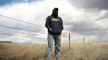 Cody Math stands next to the fence near where the Keystone XL route crosses the border from Saskatchewan into Montana on April 23, 2013. He is the fifth generation of Maths to live in the area north of Whitewater, Mont. His is the first U.S. house the pipeline route passes by. (Nathan VanderKlippe/The Globe and Mail)