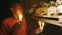 In this April 6, 2004 file photo, Apollan Odetta, a survivor from the 1994 Rwandan Genocide light candles at a mass grave in Nyamata, Rwanda. (Sayyid Azim/AP)