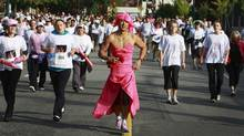 CIBC Visa employee Ivan Young sports a pink ballgown as he and nearly 13,000 other runners and walkers participate in the Canadian Breast Cancer Foundation CIBC Run for the Cure in Vancouver Oct. 5, 2008. (Jeff Vinnick/The Globe and Mail)