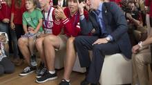 Prince Harry watches the Canadian women's eights win the silver medal in rowing Canadian silver medal rowers Malcolm Howard, centre, Jeremiah Brown and his son, Ethan during his visit to Canada House at the 2012 Summer Olympics Thursday. (Ryan Remiorz/THE CANADIAN PRESS)