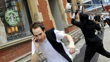 A G20 summit protester throws a chair at a coffee shop window in downtown Toronto. (Kevin Van Paassen/Kevin Van Paassen/The Globe and Mail)