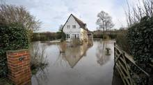 A property is surrounded by floodwater Sunday near Apperley, in Gloucestershire, after days of almost relentless downpours, Dec. 30, 2012. (Tim Ireland/AP)