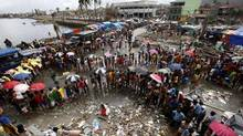 Survivors queue for food and water in the aftermath of super typhoon Haiyan in Tacloban city. The Canadian government has pledged $5-million in cash aid to assist victims of Typhoon Haiyan in the Philippines, and will match donations to registered charities. (ERIK DE CASTRO/REUTERS)