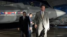 Defence Minister Peter MacKay, right, and Industry Minister Tony Clement walk past a mock-up of the F-35 Joint Strike Fighter after announcing the Conservative government's plan to purchase 65 of the stealth jets in Ottawa on July 16, 2010. (Adrian Wyld/The Canadian Press)