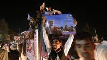 A supporter of Afghan presidential candidate Ashraf Ghani holds a poster as he celebrates in the street after the Independent Election Commission (IEC) announced preliminary results in Kabul July 7, 2014. (OMAR SOBHANI/REUTERS)