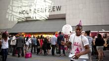 Cianan Liburd hands out party hats and noisemakers to guests at the party celebrating Holt Renfrew's 175th birthday outside its flagship Toronto store on Sept. 6. (Della Rollins for The Globe and Mail)