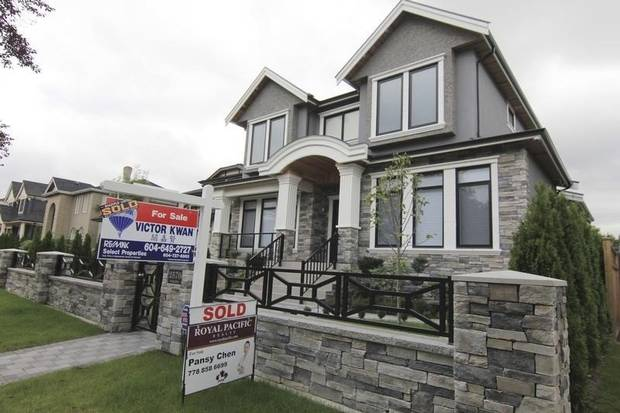 Realtors' signs are hung outside a newly sold property in a Vancouver neighbourhood on Sept. 9, 2014.