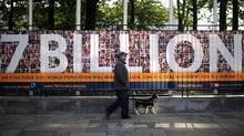 A man walks his dog past a UN sign announcing symbolically that the world population hit 7 billion on October 31, 2011. (AFP/Getty Images/EMMANUEL DUNAND/AFP/Getty Images/EMMANUEL DUNAND)