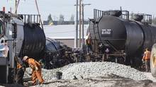 Workers prepare to empty the contents of, and then right, seven railway cars that derailed in Calgary on Sept. 11, 2013. (CHRIS BOLIN FOR THE GLOBE AND MAIL)