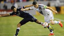 Los Angeles Galaxy forward Robbie Keane works against Vancouver Whitecaps defender Steven Beitashour during the first half at StubHub Center in Carson, Calif., on April 12. (Christopher Hanewinckel/USA Today Sports)