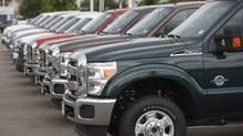 2011 Ford F-350 pickup trucks sit at a dealership (David Zalubowski/AP Photo)