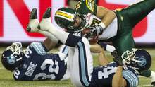 Edmonton Eskimos' J.C Sherritt (centre) intercepts as pass from Toronto Argonauts quarterback Ricky Ray as Argos Andre Durie (left) and Chad Kackert flounder during first half CFL action in Toronto on Monday August 27, 2012. (Chris Young/THE CANADIAN PRESS)