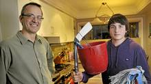 Dan Furlan, left, and his son Lukas pose in their Etobicoke home, February 18 2012. Lukas repaid his dad for his $300 hockey stick by doing house chores. (J.P. Moczulski for The Globe and Mail) (J.P. MOCZULSKI)