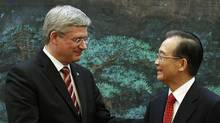 Canada's Prime Minister Stephen Harper (L) shakes hands with China's Premier Wen Jiabao following a signing ceremony at the Great Hall of the People in Beijing February 8, 2012. (CHRIS WATTIE/REUTERS/CHRIS WATTIE/REUTERS)
