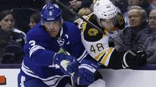 Toronto Maple Leafs' Dion Phaneuf checks  Boston Bruins' Chris Bourque during the first period of their NHL hockey game in Toronto February 2, 2013. (Reuters)