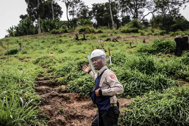 Choem Bo, HALO's supervisor in Pailin province, prepares to enter a minefield. The crudely made steps cut into the side of the hill are the only safe place to walk; the red and white sticks mark land that has not been cleared.