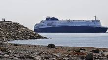 Two people on Deer Island watch as the Nova Star cruise ferry makes its way into Boston Harbor, Monday, May 12, 2014, for a christening ceremony. (Elise Amendola/AP)